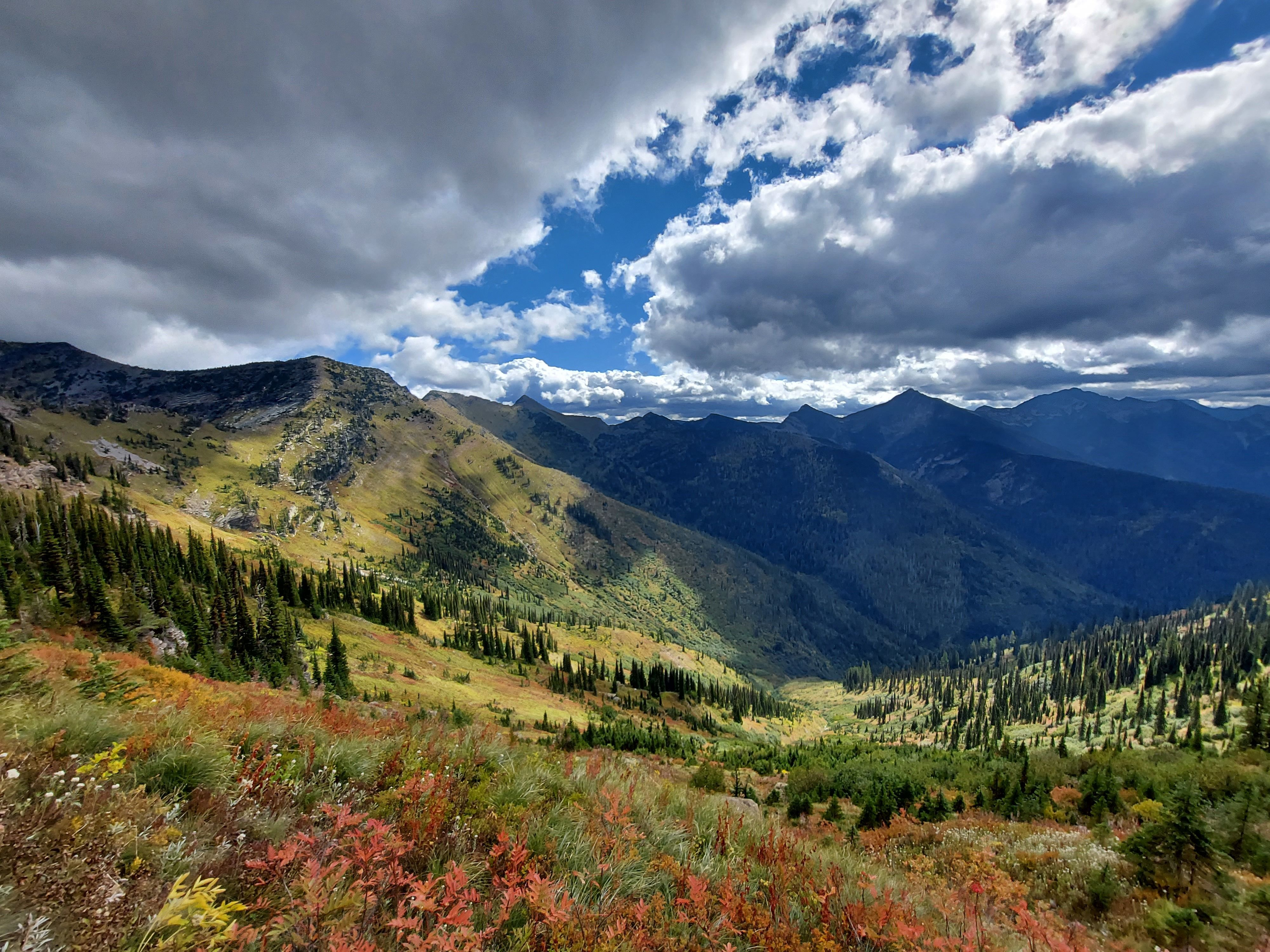 Green rolling hills, dotted with red fall colors and a partly cloudy sky