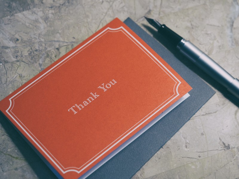 Orange thank you card with pen sitting next to it