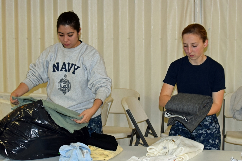 Midshipmen 4th class Victoria Ramirez-Solis and Michelle Katz sort and fold clothing.