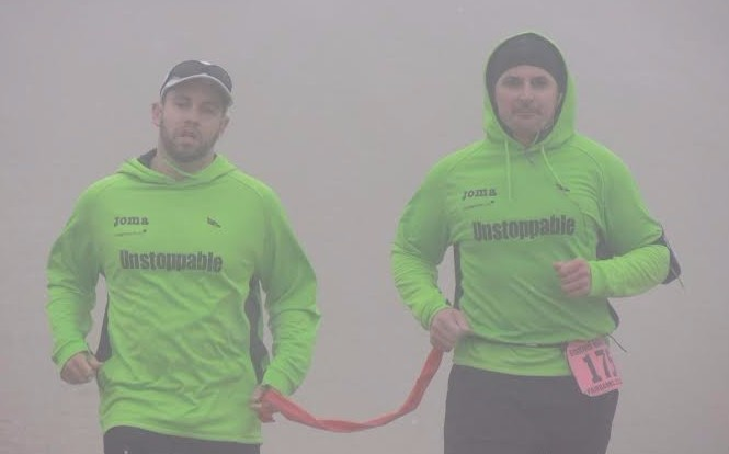 Picture of Brian Switzer and his Guide Marco running while wearing green sweatshirts that read: Unstoppable