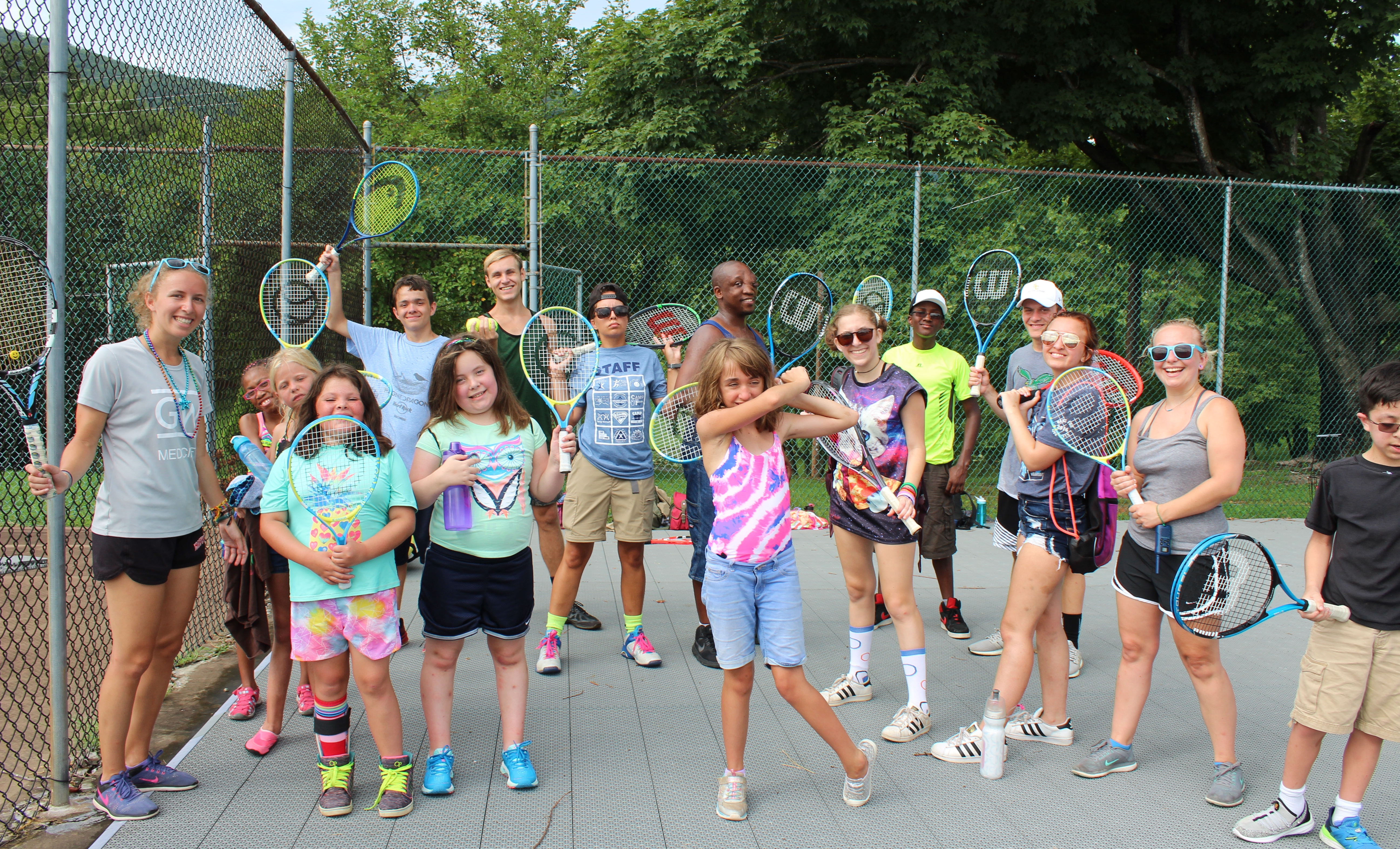 Campers hold tennis rackets and pose for a photo.