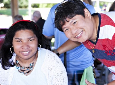 (Left) Woman in wheelchair smiling. (Right) PSRS employee leaning in and smiling