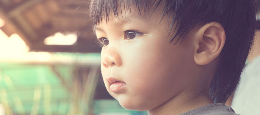 Close up image of a small boy facing left and staring