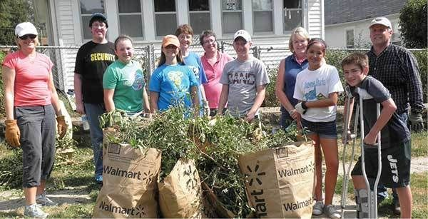 Group of volunteers cleaning up lawns.