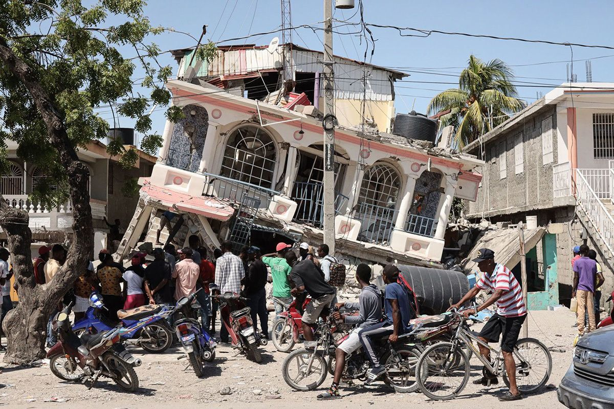 Residents of Les Cayes, Haiti, survey a damaged structure on Sunday, August 15, a day after a 7.2 magnitude earthquake struck the country.