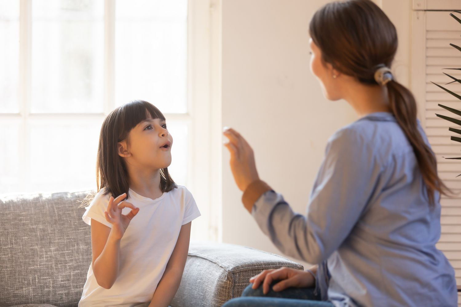 Counselor doing sign language with a young girl.