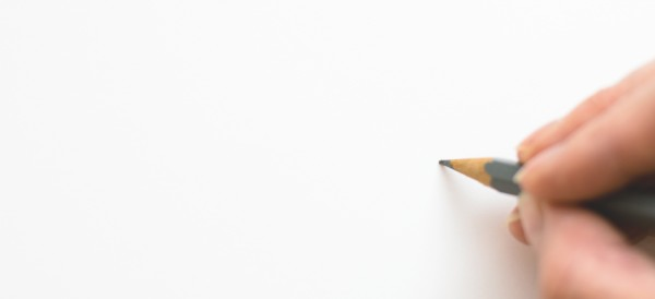 Person holding pen to paper, ready to draw an illustration