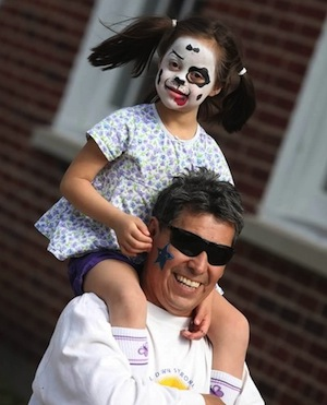 Girl child on her dad's shoulders at a past Buddy Walk for Down syndrome event.