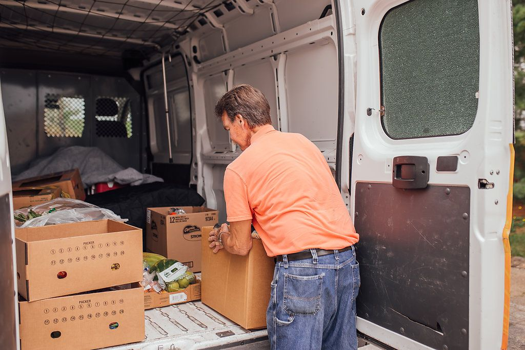 Man loading boxes of food into the back of van.