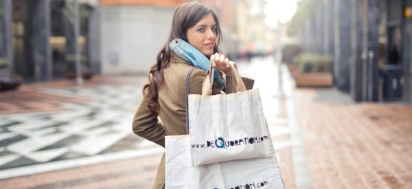 Woman walking down the street while holding 2 shopping bags