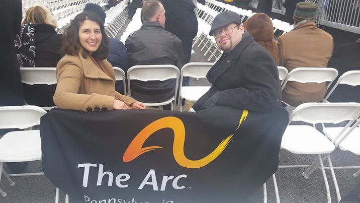 Matt and Ashlinn Sitting at Inauguration with The Arc of PA BAnner