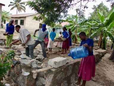 Group of people working on building cement wall.