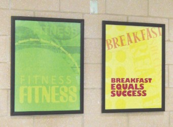2 poster images in school hallway, healthy message in text, green, yellow, custom signs