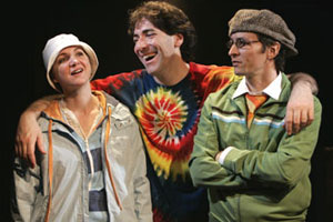 Pamela is wearing a rain jacket, a striped hoodie, and a white hat. She's smiling. Nicholas is wearing a tye-dye shirt while smiling, putting his arms around his friends. Nick is wearing a green jacket.
