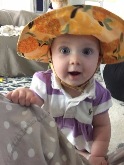 Photo of 1 year old Emma wearing a yellow sun hat and big smile on her face.