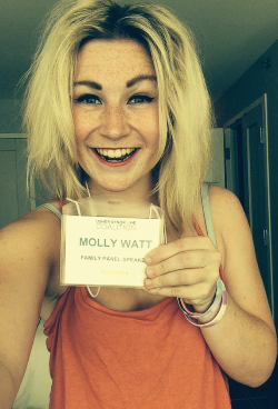 Molly Watt smiling and holding her USH2014 name badge