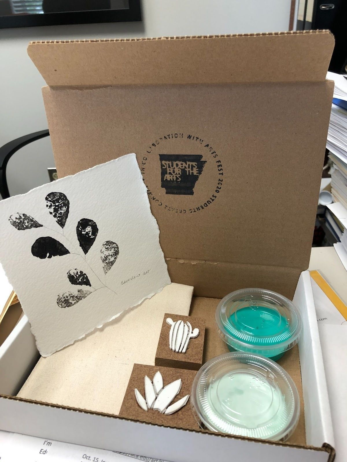 A Students for the Arts branded box contains supplies for a self-care arts project using paint and stamps.