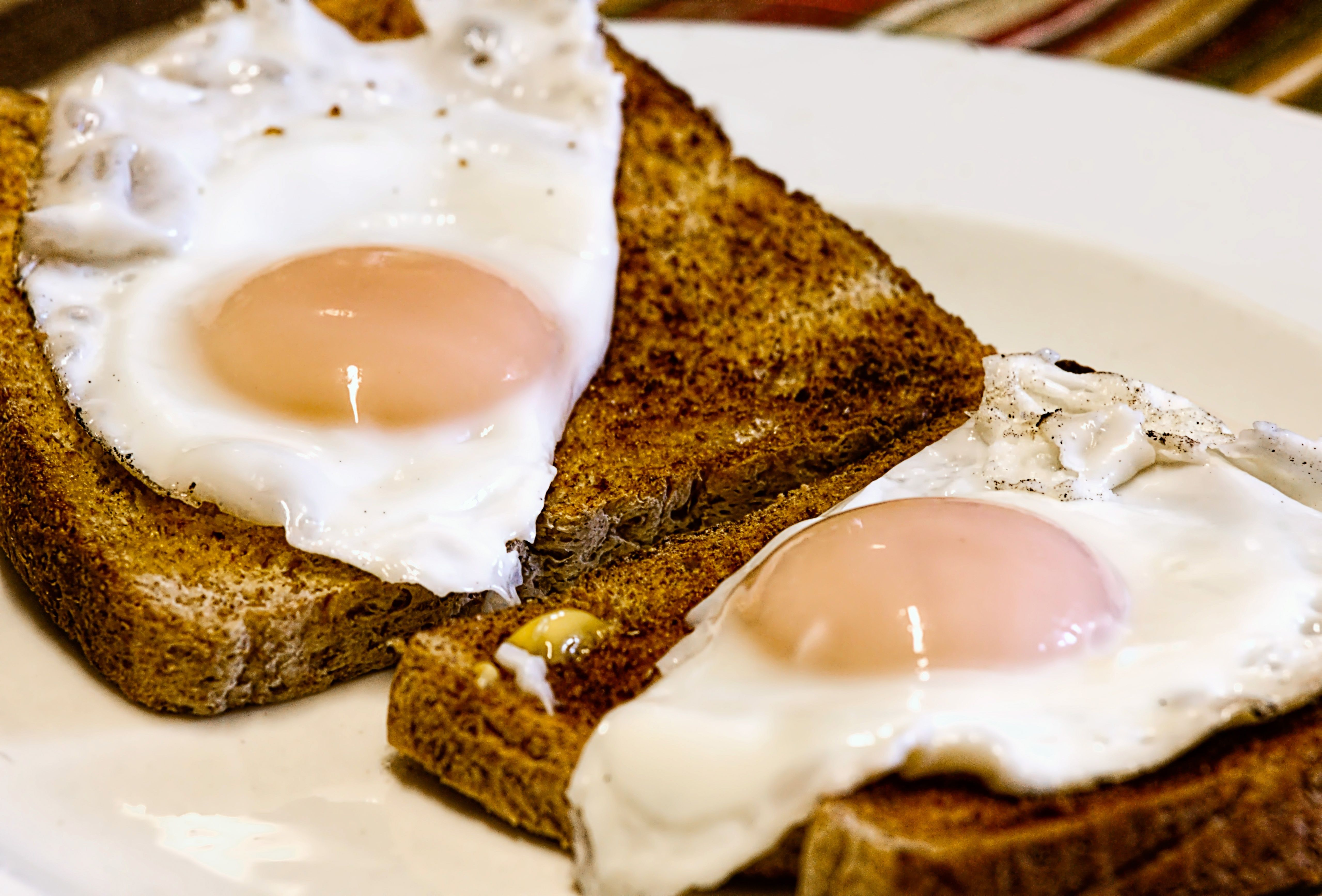 Two sunny side up eggs on pieces of toast