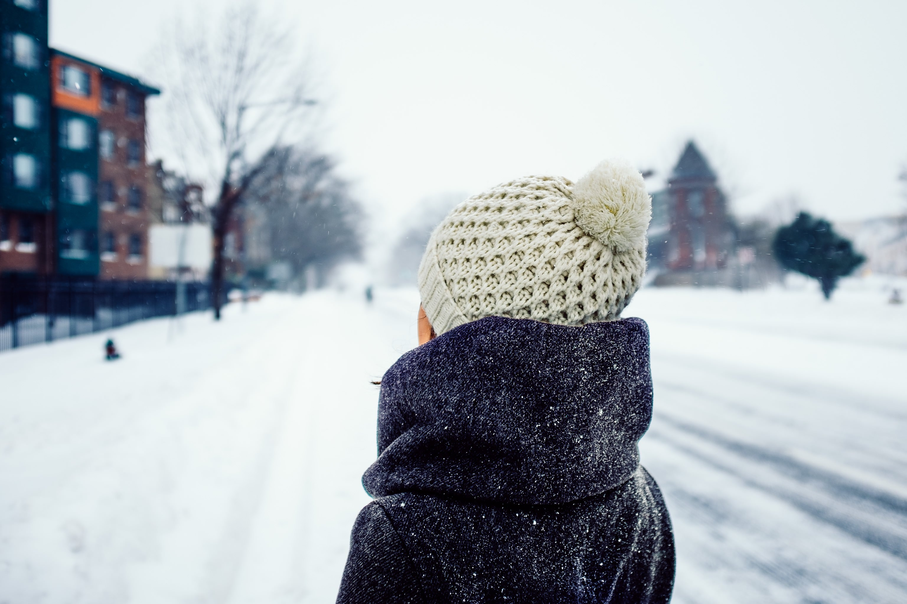 Pictured: Girl bundled up in warm clothing standing outside as snow falls.