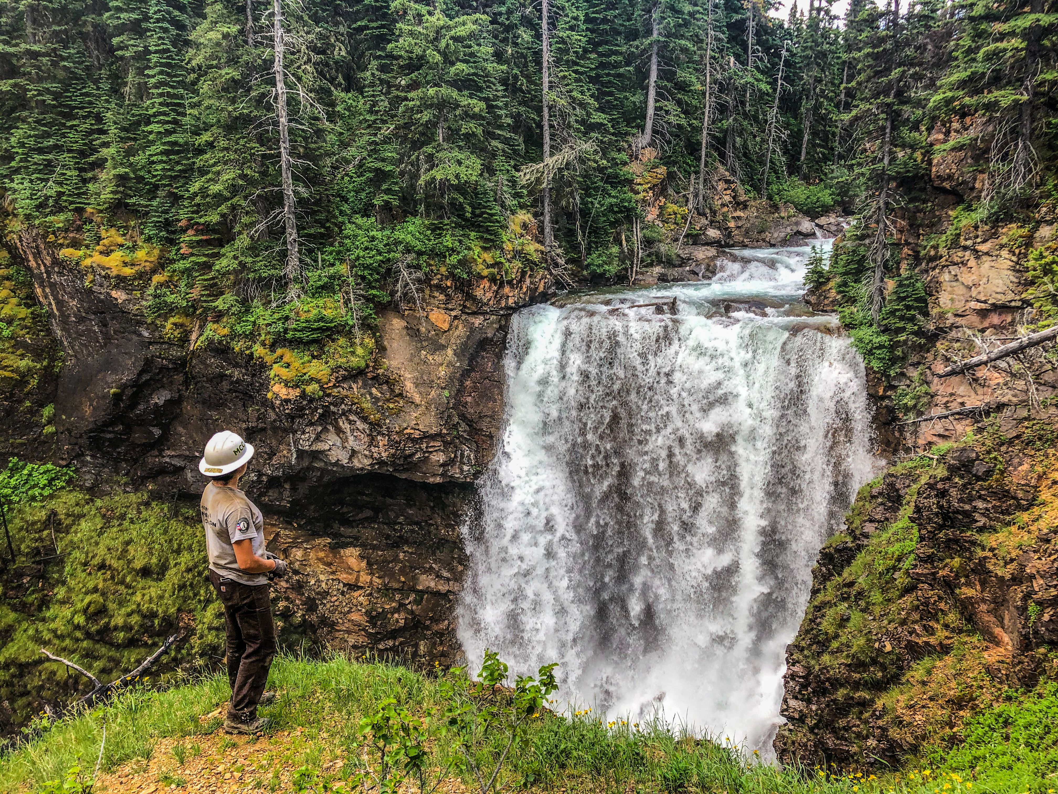 Crew member with MCC gear watching a beautiful waterfall enjoying the outdoor beauty