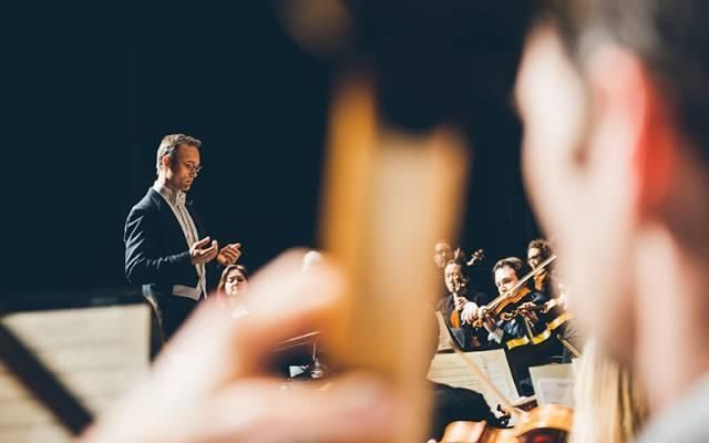 A photograph from the back of the string section of an orchestra, a male orchestral conductor in a tuxedo stands at the podium directing the ensemble
