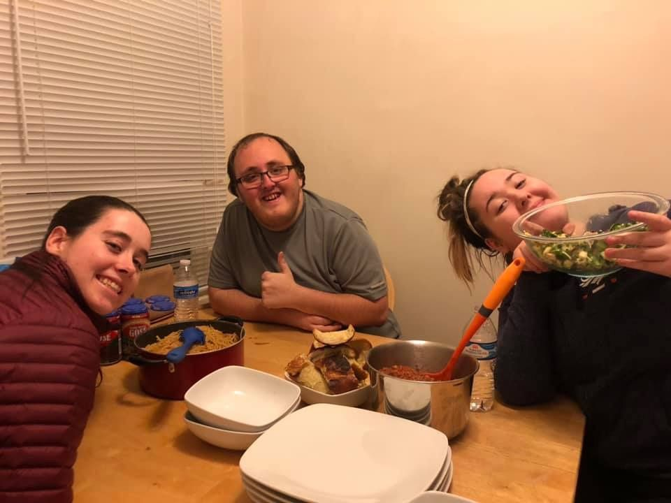 Three students in apartment eating pasta dinner