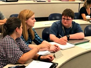 Three students, one with a disability, sit in classroom doing group work
