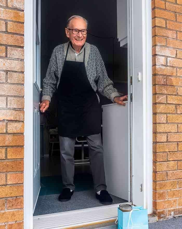 Elderly man at door.
