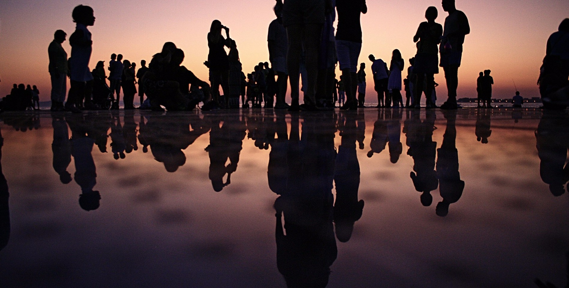 A silhouette of a group of people on a beach at dusk