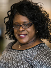 Professional photo of black woman with curly hair and glasses smiling