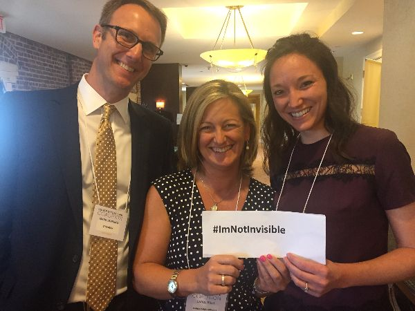 Photo of Mark Dunning, Carol Brill and Krista Vasi holding a sign that reads #ImNotInvisible