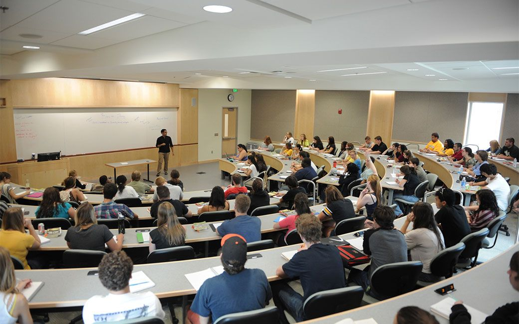 Students seated facing whiteboard in semi circle style lecture hall