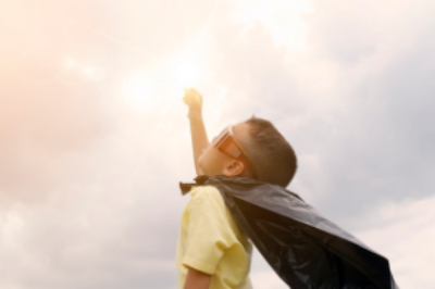 Young boy with cape and fist raised mightily to the sky