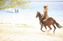 This is a picture a girl riding a horse on the beach
