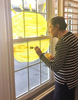 Resident painting a window