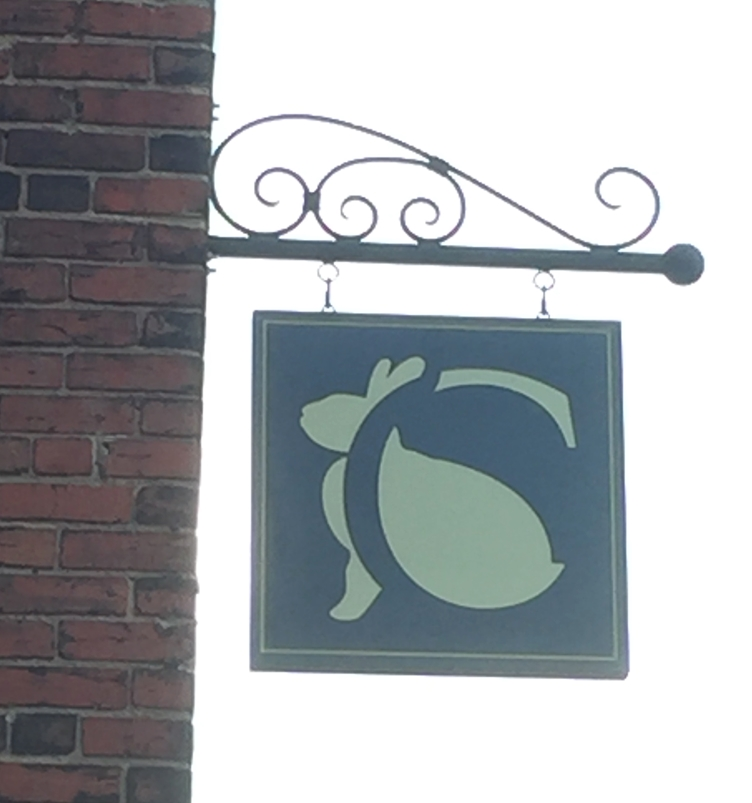SA28498 - Engraved Sign Featuring the Store's Logo (a Rabbit)  for a Retail Store, Hung from a  Scroll Bracket