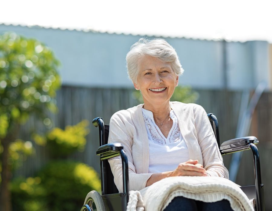 Older woman sitting outside in her wheelchair smiling at the camera