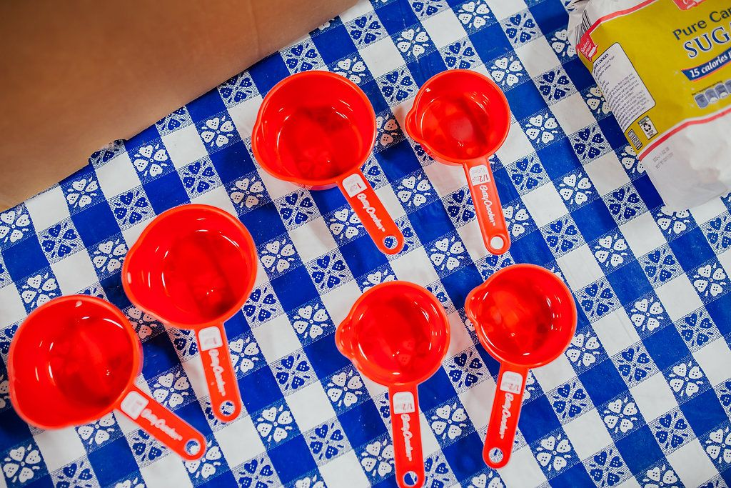 Various size measuring cups on a blue and white tablecloth.