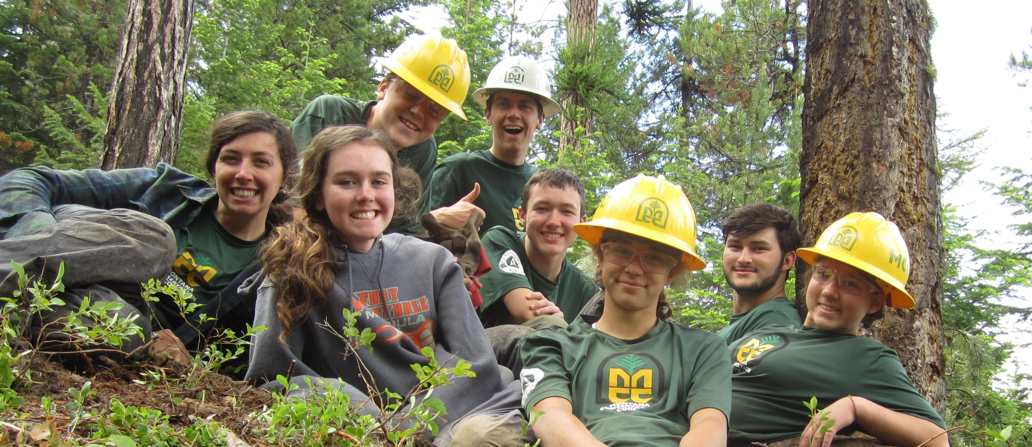 Seven youth in the forest and are wearing green MCC t-shirt made with wicking material, both boys and girls and three have on the yellow MCC helmet and 1 has a white helmet and is a young adult leader for the youth program.