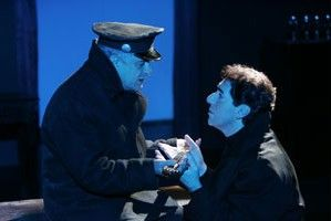 George is wearing a black jacket and a police hat. He's facing Nicholas who is kneeling and wearing a black jacket. Nicholas is reaching his hands out. They're exchanging something in Nicholas' hands. The lighting in this scene is blue.