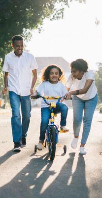 Parents Helping Child on Bike