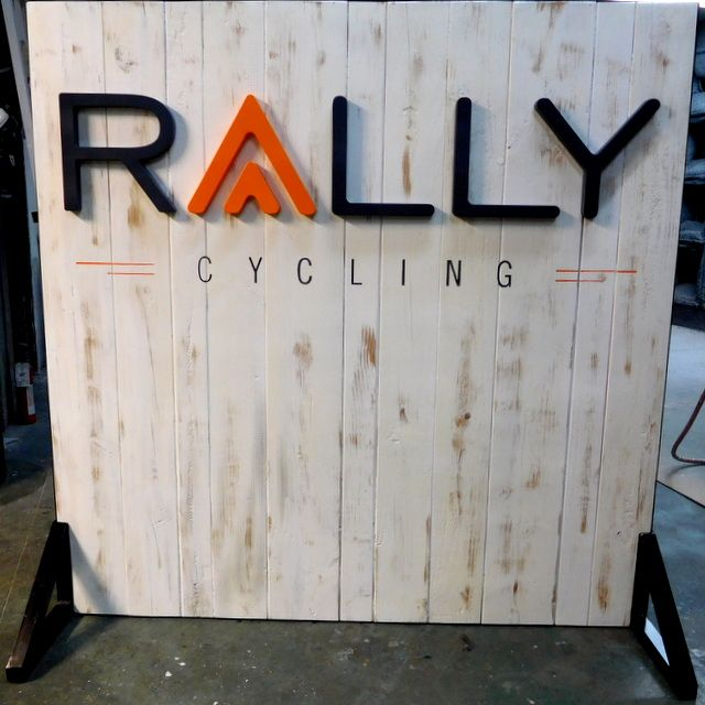 """S28012 - Self-Standing Carved Cedar Wood Sign for  """"Rally Cycling """", with .Cut-out Letters"""