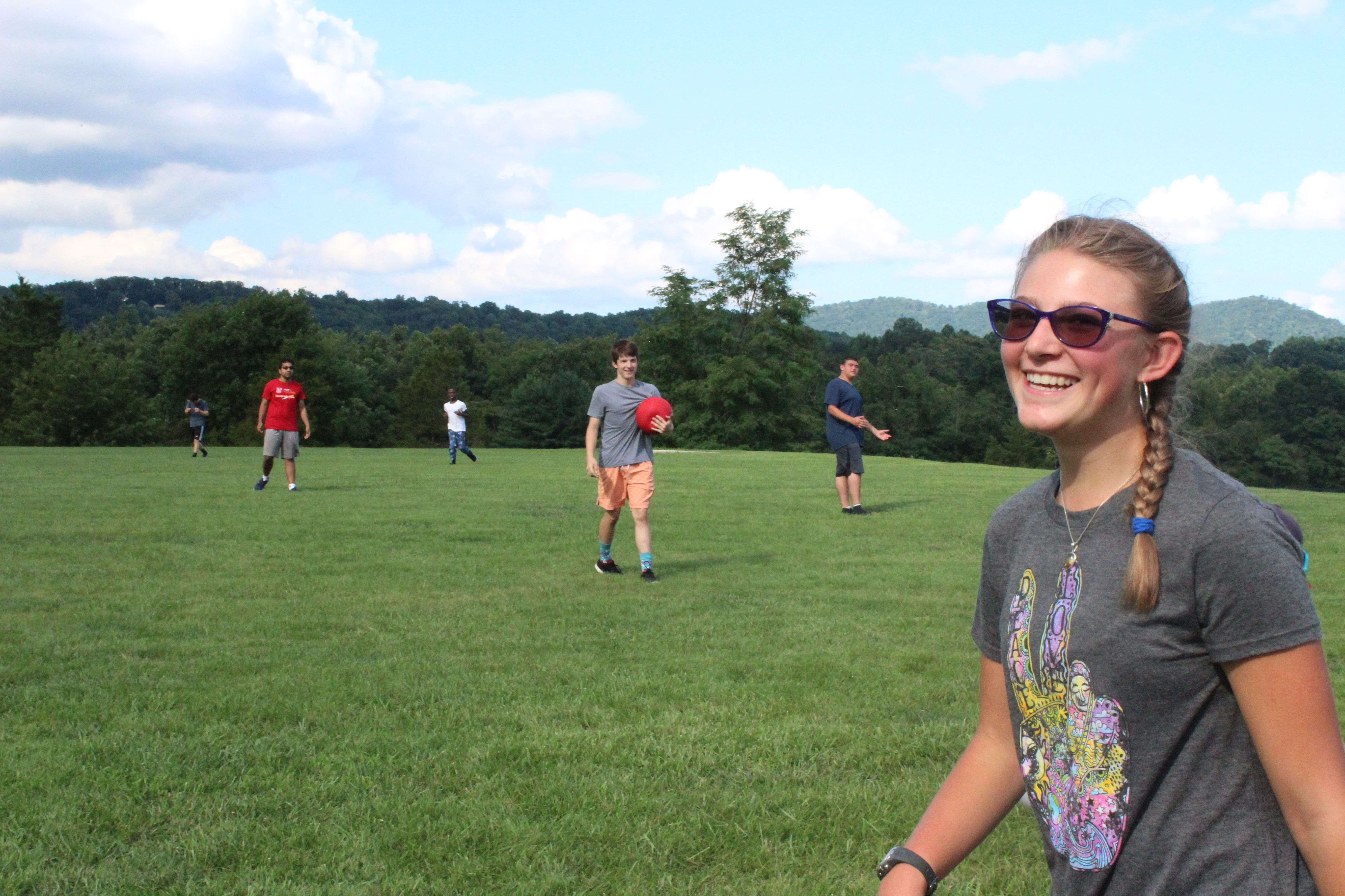 A camper smiles during a game of kickball.