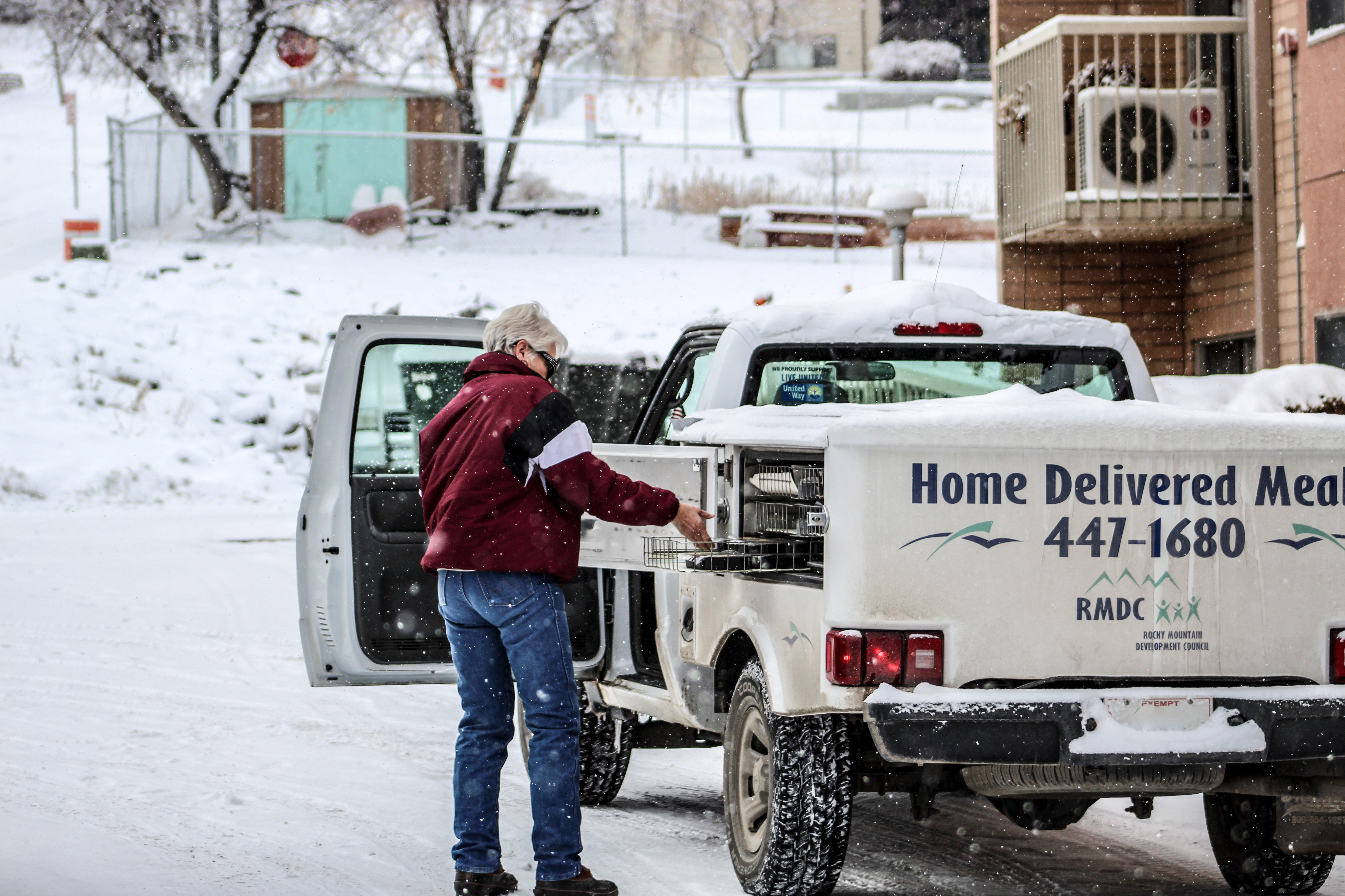 Pictured: Meals on Wheels driver, Duzzy, delivering meals on a snowy, winter day.