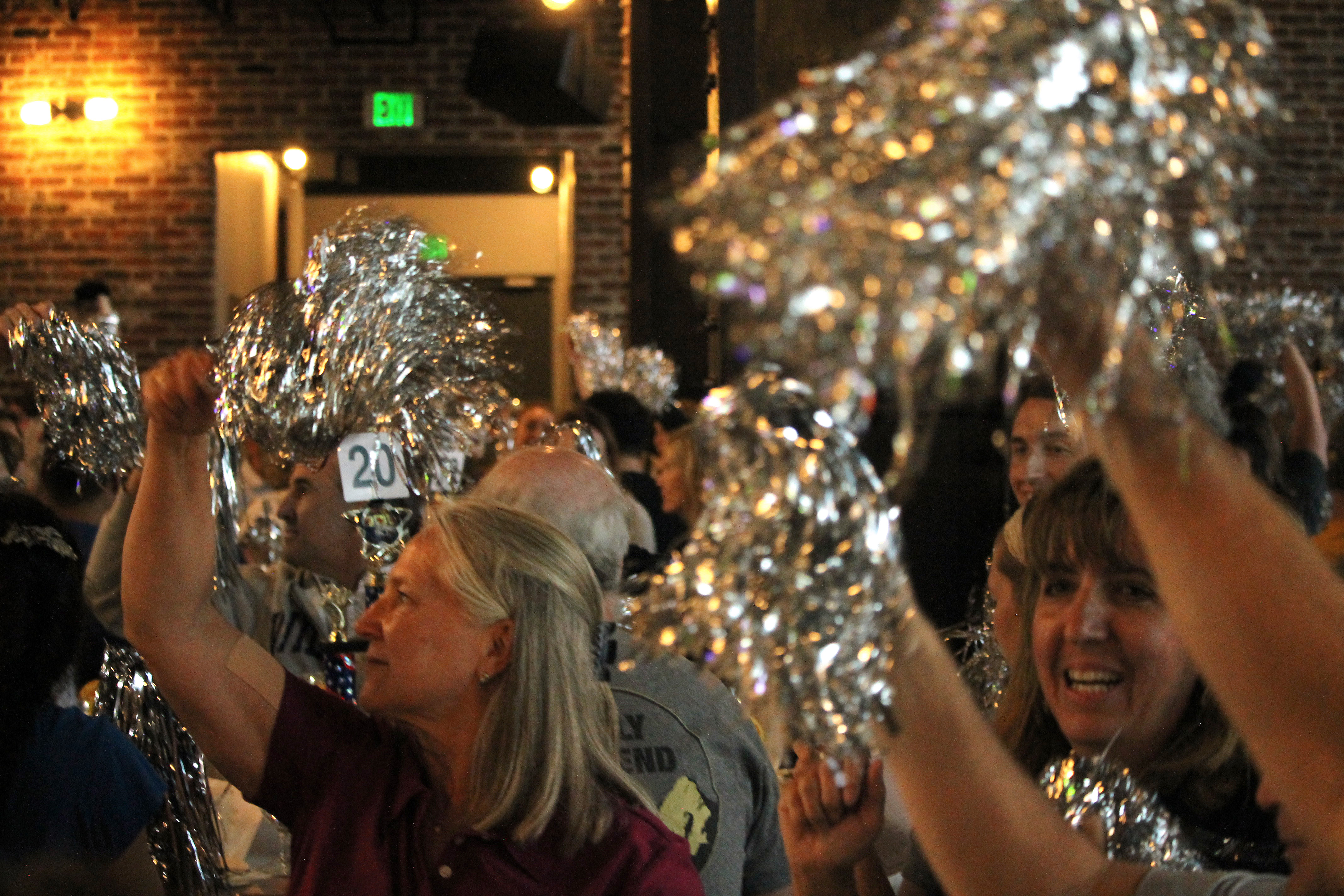 Room full of people wave silver pom poms in the air