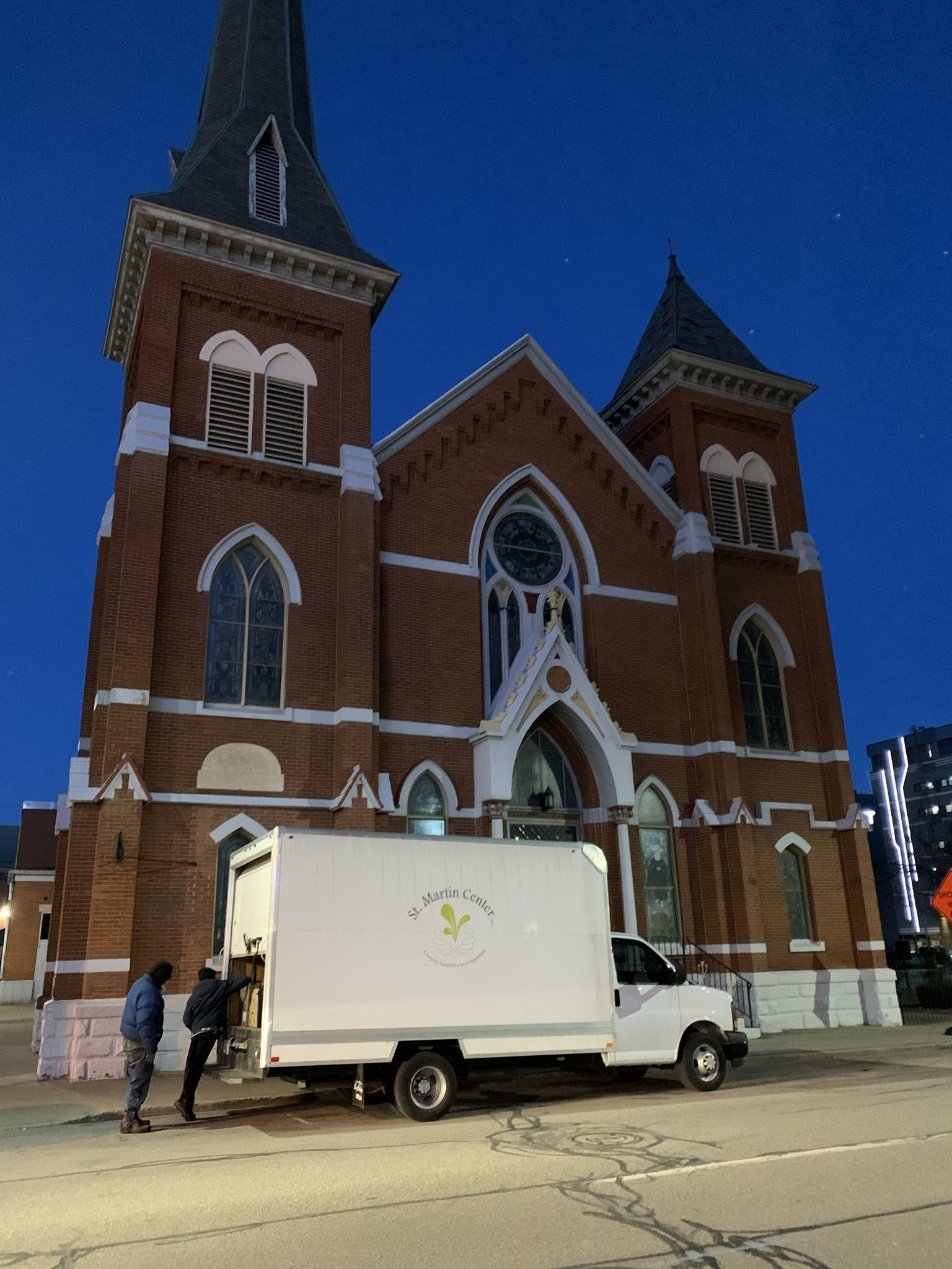 Two men stand together at the back of a large box truck parked in front of a church.