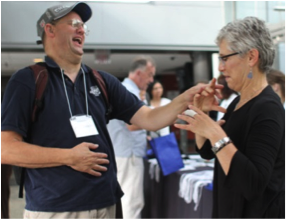 A picture of two people greeting each other at the usher syndrome conference.