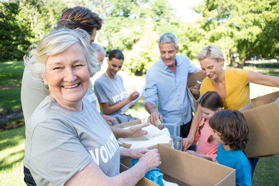Female older adult smiling at the camera during a volunteer event. A family is looking at items behind her.