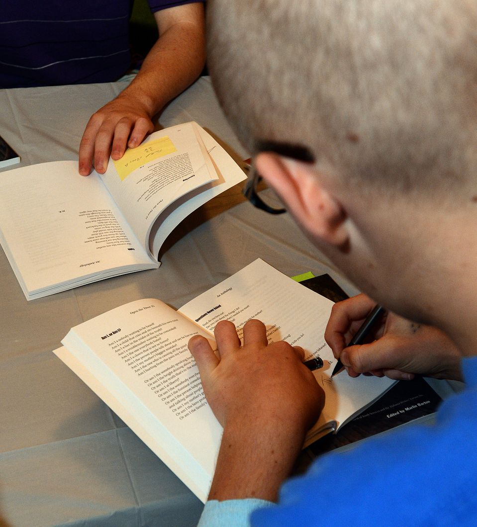 Student writer autographs a book.