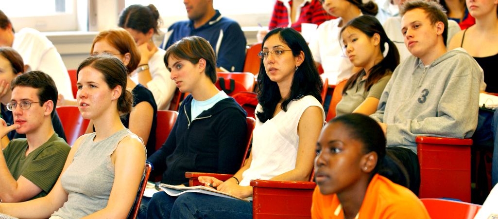 Students sit in rows in lecture style classroom